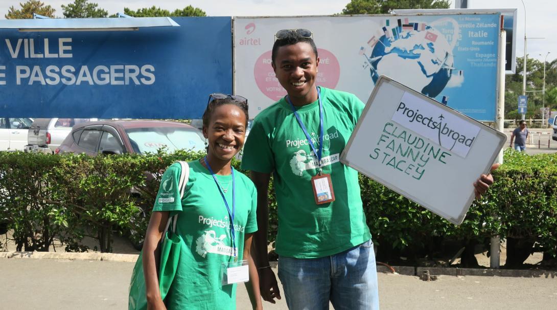 Projects Abroads personal möter upp volontärer på flygplatsen med en skylt och stora leenden.